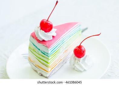 Rainbow crape cake with cream and cherry , selective focus