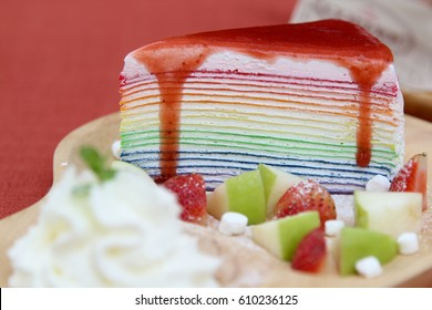 Rainbow crape cake and fruit on wooden plate.