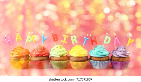 Rainbow cupcakes with HAPPY BIRTHDAY candles on color background