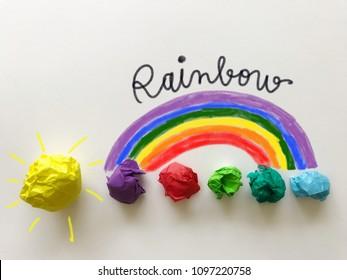 Rainbow doodle drawing with colorful papers on white background