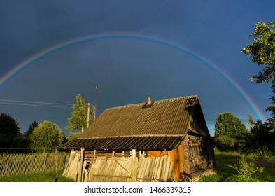 Rainbow in the dramatic sky over an old boarded-up log house in the countryside