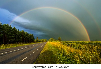 Rainbow and dramatic sky over road in Estonia