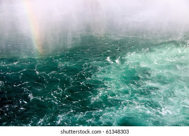 A rainbow emerging from rough and choppy water.