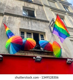 Rainbow flag LGBT pride and rainbow umbrellas on a house in Marais quartier in Paris, France, gay district placed Paris