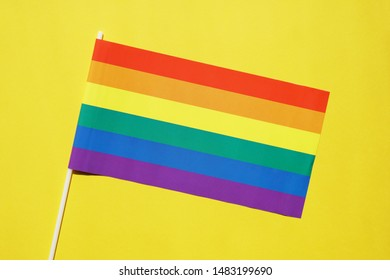 rainbow flag on yellow background - lgbt or gay pride symbol - lesbian homosexual bisexual transgender queer