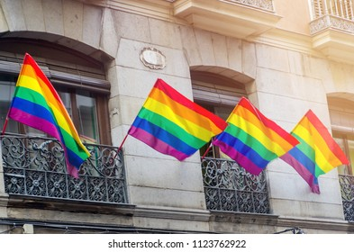 rainbow flags waving on balconies in the streets of Madrid during gay pride party