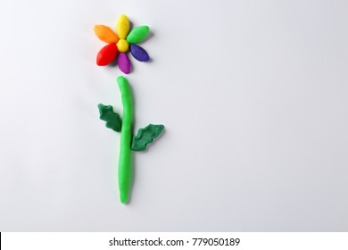 Rainbow flower made from plasticine on white background