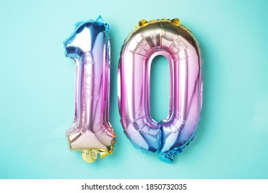 Rainbow foil balloon number, digit ten. Birthday greeting card with inscription 10. Anniversary concept. Top view. Colored numeral on blue background. Numerical digit, Celebration event, template.