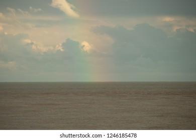 rainbow forming on the sea