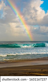 Rainbow forming at sunrise over the pacific waves breaking at the world famous surf reef known as Banzai Pipeline on the north shore of the hawaiian island of Oahu