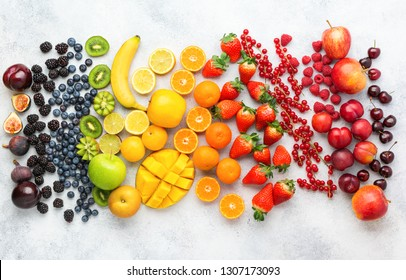 Rainbow fruits berries background on white. Top view of strawberries blueberries cherries mango apple lemons oranges red currants plums blackberries, selective focus