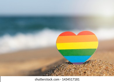 Rainbow gay flag heart on the beach. LGBT concept.  LGBT equal rights movement and gender equality concept. Copy Space. Romantic trip gay honeymoon