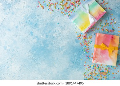 Rainbow gifts with candy confetti on blue background. Flat lay, top view. Copy space