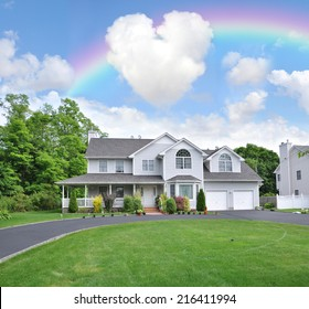 Rainbow and heart shaped clouds over Suburban Mcmansion style home in residential neighborhood Blue Sky Clouds USA