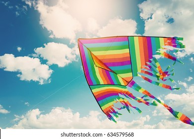 Rainbow kite flying in blue sky with clouds. Freedom and summer holiday concept