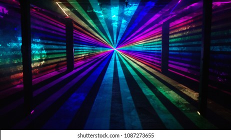 Rainbow laser beams shine from a central point past four silhouetted columns on an otherwise empty background. Music festival / nightclub / heaven
