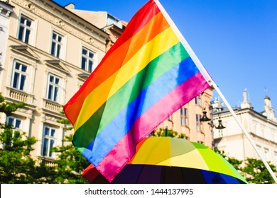 The Rainbow LGBT Pride Flag Blows against Blue Sky and rainbow umbrella over Pride Parade in Cracov, Poland.