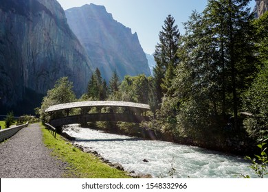 Rainbow light on wooden bridge above white stream of water with mountain and forest backdrop