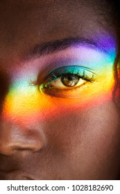 Rainbow light over eye of beautiful woman, close up