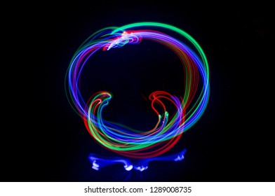 Rainbow light trails form a circle on a black background