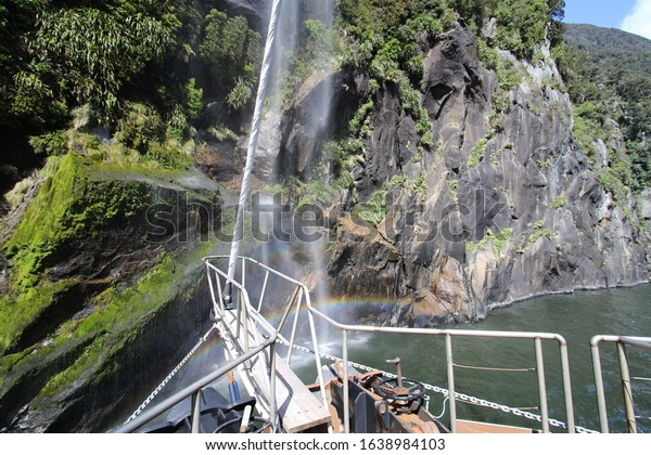 Rainbow mirroring on waterfal during ship tour at milford sound, new zealand