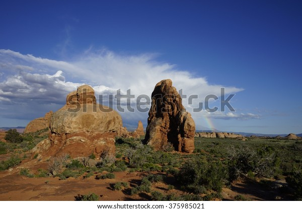 A rainbow near the Windows at Arches National Park near Moab, Utah, USA.  A few clouds break up a beautiful blue sky day in the springtime at this tourist destination in the high desert.