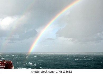 Rainbow in the ocean after rain and thunderstorms. Colorful views of the rainbow against the sky, clouds and sea horizon.