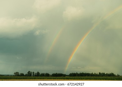 Rainbow on the cloudy sky after the rain. Abstract nature wallpaper.