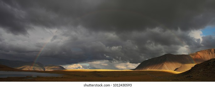 Rainbow on the shore of a mountain lake, panorama landscape