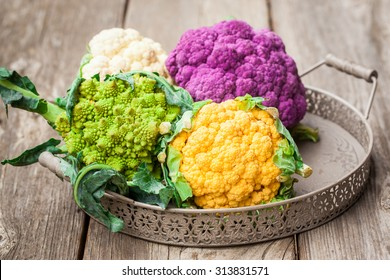 Rainbow of organic cauliflower and Romanesco broccoli on wooden table. Also available in vertical format.