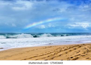 Rainbow over beach and waves hitting the shore, Kauai Hawaii
