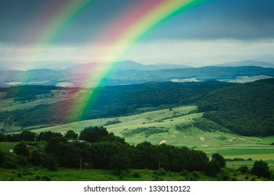 rainbow over beautiful green summer landscape after rain, fresh green meadows and hills in serene landscape