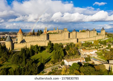 Rainbow over Cite de Carcassonne. Old medieval hill-top citadel in the French city of Carcassonne, fortified by two castle walls. Aude, Occitanie, France. Aerial view. Pyrenees mountains background.