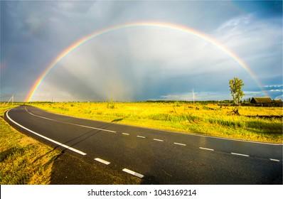 Regenbogen auf ländlicher Autobahn Frühjahrslandschaft