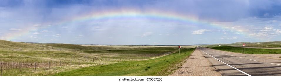 Rainbow over the highway in Saskatchewan. Saskatchewan, Canada.