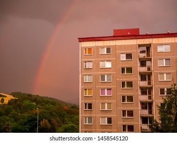 Rainbow over the house with dense rain clouds in the background