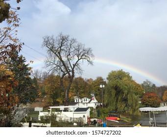 Rainbow over houses, trees, and lake in Wynantskill NY.