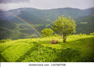 Rainbow over the mountains in Tatev, Syunik Province of Armenia. Mountain landscape in Armenia. Big green tree and the lonely bench next to the rainbow, Armenia