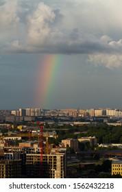 Rainbow over new areas of Saint Petersburg. Thunderstorm sky. Buildings under construction.