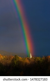 A rainbow over a New  church steeple in Middlebury, Vermont during a fall season sunset.