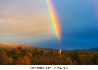 A rainbow over a New England church steeple in Middlebury, Vermont during a fall season sunset.