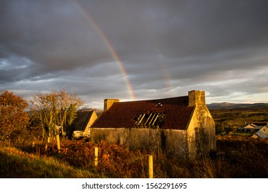 A rainbow over an old Irish house in Donegal, Ireland.  A cloudy day and the house has a hole in the roof.