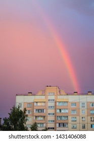 Rainbow over the roof of a multi-storey city house in the evening pink sunset sky after rain, summer fantastically beautiful magical landscape, vertical shot