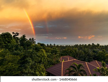 Rainbow over roofs of houses, trees and the sea against the backdrop colourful sunset on a tropical island