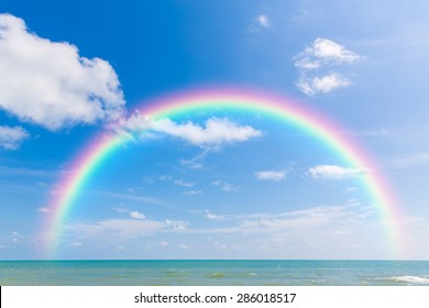 Rainbow over sea with blue sky and cloud.
