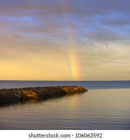 A rainbow over the sea in the sunset
