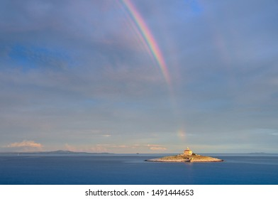 Rainbow over small Island with Lighthouse  - Shutterstock ID 1491444653