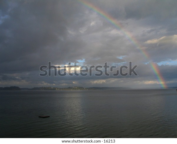 Rainbow over the southern end of Puget Sound, taken from Home (Lakebay), Washington, looking southeast towards Mount Rainier, which is hidden behid the clouds in the center. Landscape orientation.