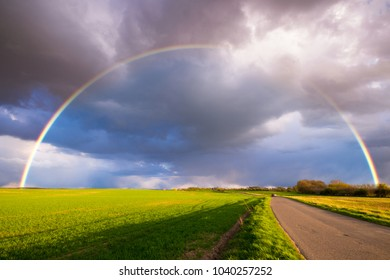 Rainbow over the spring field after the evening storm