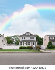 Rainbow over suburban home with american flags in residential neighborhood USA blue sky clouds